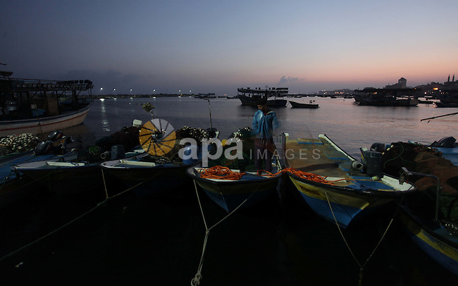 A Palestinian fisherman works on his boat during the sunrise at the Gaza seaport in the west of Gaza City, 02 September 2013. The Egyptian navy boats attacked the Palestinian boats off the southern Gaza Strip last Friday, near the border with Egypt, wounding fishermen and the arrest of 5 fishermen. Photo by Ashraf Amra