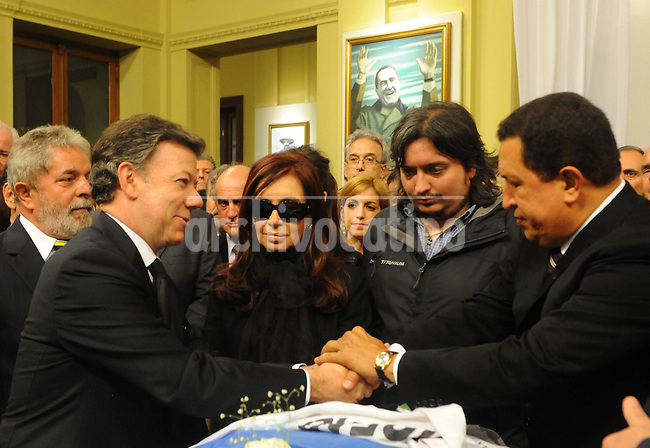 Presidents of Colombia Juan Manuel Santos, left, shake hands with Venezuelan Hugo Chavez, while President of  Argentina  Cristina Fernandez and her son Maximo looks on during the funeral of her husband Nestor Kirchner at Presidential Palace in Buenos Aires,  Thursday, October 28, 2010.
