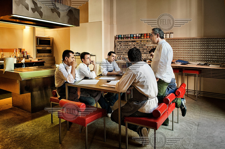 Chef Ferran Adria (right, kneeling up) of El Bulli restaurant, in his workshop working with his team on new recipes.
