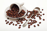 Coffee beans spilled cup spoon saucer on white background