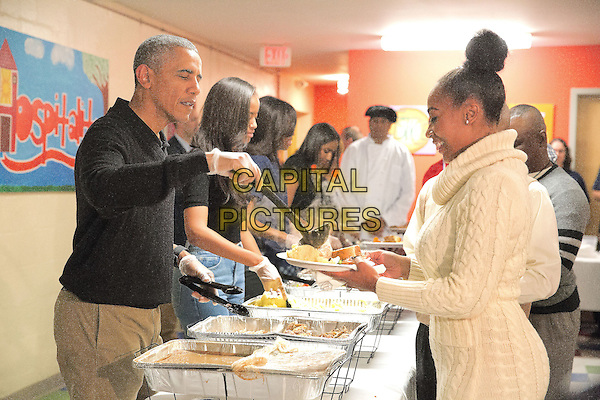 United States President Barack Obama and family serve Thanksgiving meals to homeless and at-risk veterans at the Friendship Place homeless center in the basement of St. Luke's Methodist Church, in Washington, DC, Wednesday, November 25, 2015.  As part of the Administration's focus on reducing the rate of veteran homelessness, Friendship Place received a $3.1 million grant from the Department of Veterans Affairs in 2015.  From left to right: President Obama, Malia Obama, first lady Michelle Obama, Sasha Obama. <br /> CAP/ADM/CNP/MHS<br /> &copy;MHS/CNP/ADM/Capital Pictures