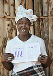 A woman who participates in a community microcredit program in Kavuzi, Malawi, proudly shows the passbook where she records her savings.