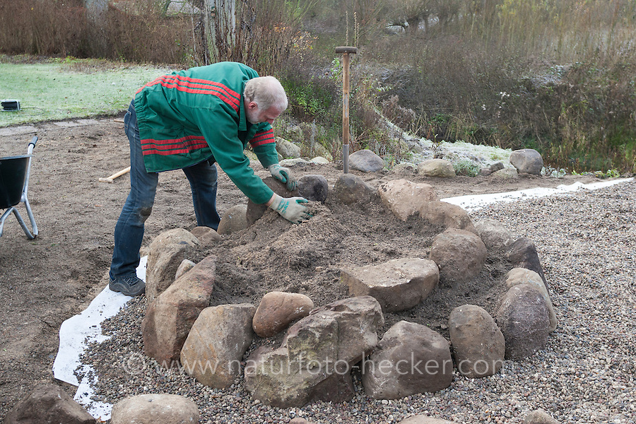 Bau einer Kräuterspirale aus Feldsteinen, Kräuterbeet, Beet, Kräutergarten, Gartenarbeit. Verlegen der nächsten Steinreihen