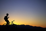 A lone mountain biker is silhouetted at sunset in the Wasatch Mountains of Utah.