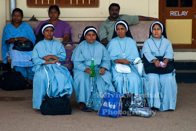 Local Catholic Nuns wearing their Habits waiting for the train to arrive. Alleppey Railway Station, Kerala Backwaters - Southern India.