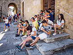 Lunch in the shade on the steps of Duomo di San Gimignano, San Gimignano, Siena-Tuscano, Italy