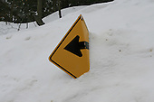 Sharp right turn in road sign, partially buried in snow bank, heavy snowfall in Quebec