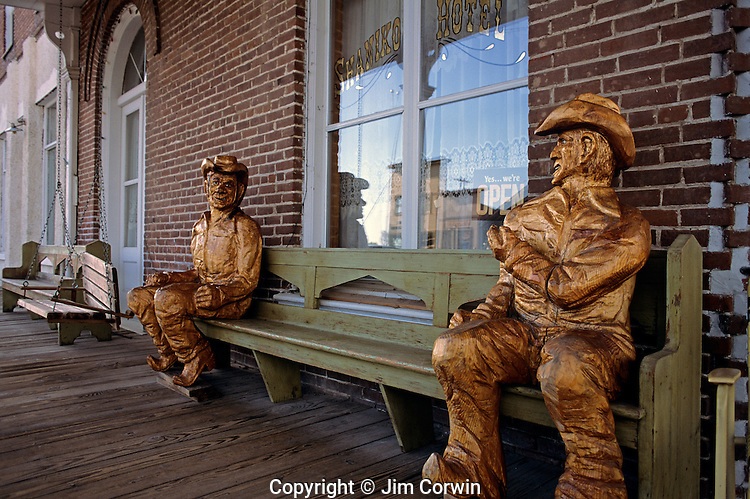 Two old cowboy sculptures sitting on a bench in front of store shops in the ghost town of Shaniko Central Oregon State USA