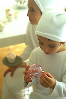 A boy sits playing with a pink glass Christmas decoration and next to him his brother holds a cupcake on a plate