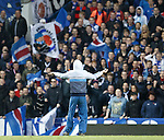 A supporter comes onto the park and tries to wind up the Rangers fans