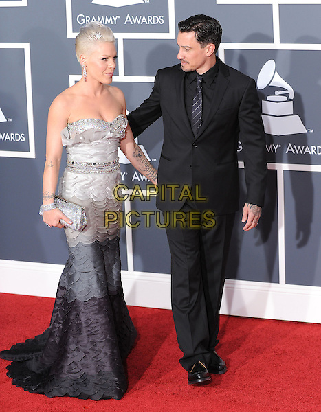 PINK (ALECIA MOORE) & CAREY HART.Arrivals at the 52nd Annual GRAMMY Awards held at The Staples Center in Los Angeles, California, USA..January 31st, 2010.grammys full length black grey gray strapless dress hand on hip piink pinnk beads beaded silver clutch bag dip dye dangling earrings suit married husband wife .CAP/RKE/DVS.©DVS/RockinExposures/Capital Pictures