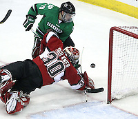 UNO goalie John Faulkner dives to knock the puck away from North Dakota's Evan Trupp during the second period. No. 4 UNO beat No. 7 North Dakota 1-0 Saturday night at Qwest Center Omaha. (Photo by Michelle Bishop)