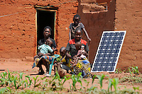 Afrika ANGOLA Kwanza Sul, Dorf Cassombo, Familie mit Solarpanel vor ihrer Lehmhuette / ANGOLA Kwanza Sul, village Cassombo, family with solar panel in front of their hut