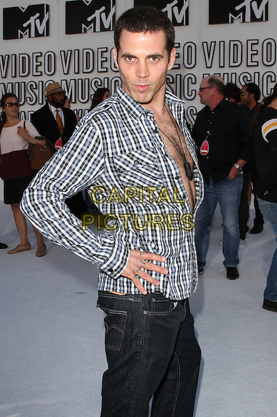 STEVE-O (Stephen Gilchrist Glover).2010 MTV Video Music Awards held at the Nokia Theatre L.A. LIVE,  Los Angeles, California, USA, .12th September 2010..VMAS Arrivals half length plaid checked check shirt jeans grey gray hairy chest necklace hand on hip .CAP/ADM/KB.©Kevan Brooks/AdMedia/Capital Pictures.