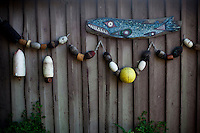 Some native artwork hangs with some fishing buoys on the walls of a cabin on Lopez Island, WA, USA.