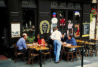 L'Ecurie (The Stable) Restaurant waiter in blue jeans serves guests at sidewalk tables. Chalkboard menu. Whimsical animals painted on windows. Paris, France.