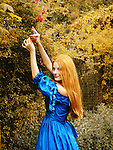 A woman in a blue romantic gown, with bright red hair and a smiling facial expression, holding a rose from a bush in the garden.