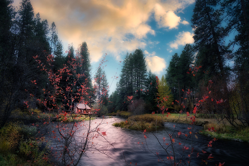 Sunset in fall on Metolius River with cabin. Oregon
