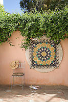 A glittering circular panel of mosaic tiles on a courtyard wall