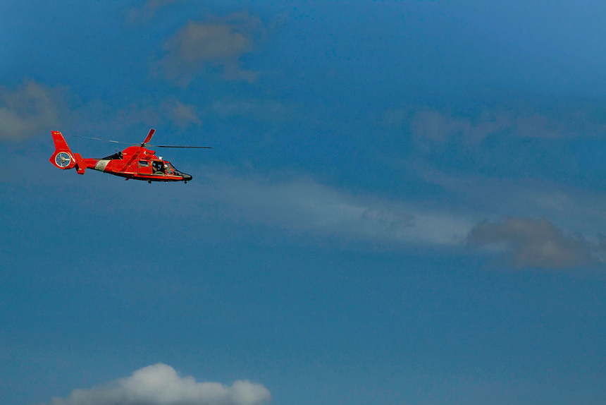 Navy Coast Guard helicopter flying high in a blue sky.