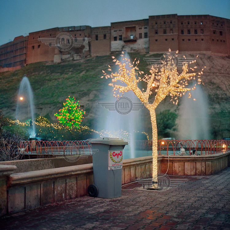 A tree decorated with electrical lights stands next to a fountain below the ancient Citadel of Arbil. The Citadel of Arbil is an inhabited mound in the centre of the modern Iraqi city of Erbil, which is said to be one of the oldest, continually inhabited places in the world. Earliest traces of habitation on the mound date back to the 5th millennium BC, possibly earlier. The city of Erbil, the fourth biggest in Iraq, is today the capital of Iraqi Kurdistan. .Since 2007 the High Commission for Erbil Citadel Revitalisation (HCECR) has been in charge of the Citadel complex and is carrying out major reconstruction efforts since moving out all remaining residents. It is hoped that 50 families will move back into the Citadel once renovation work and archeological digs have been completed. .