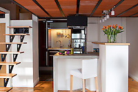 This contemporary kitchen is made up of three distinct areas.  One wall conceals the sink, with the fridge, oven and open shelving along another, while a central block of waxed concrete doubles as a work surface and breakfast bar for eating on the run