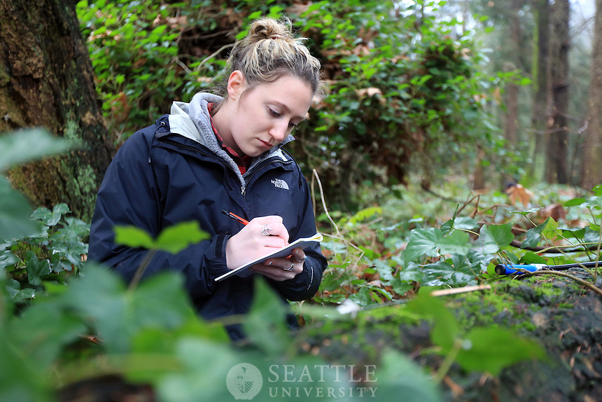 02022013- Junior Environmental Science major Mackenzie Cox writes down her measurements in her field notes after taking a tree core sample during professor Lyn Gualtievis's field methods class in the woods on Mercer Island.