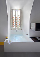 A low concrete bath has been created in the narrow alcove created by the vaulted walls of this former convent, with an open minimal fireplace beside it