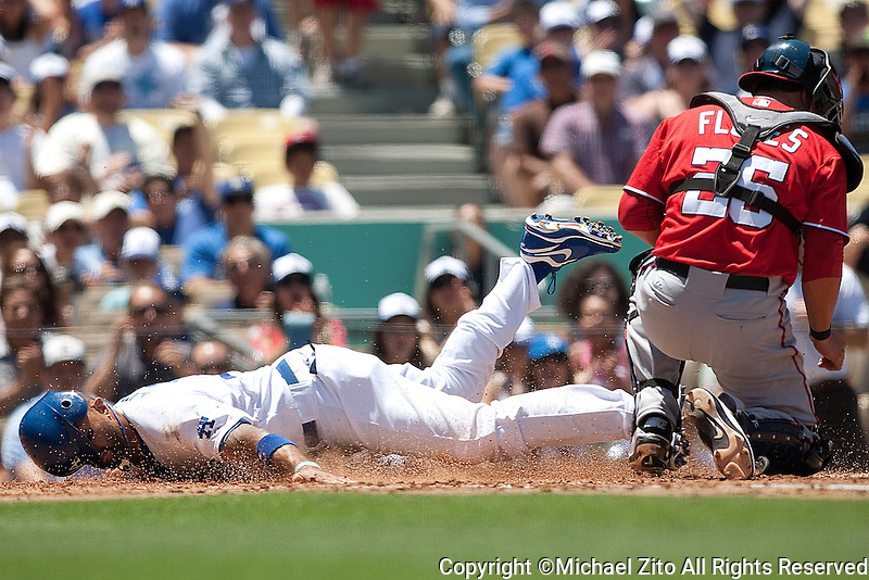 07/24/11 Los Angeles, CA: Los Angeles Dodgers Matt Kemp #27 slides safely home past Washington Nationals catcher Jesus Flores #26 during an MLB game played at Dodger Stadium. The Dodgers defeated the Nationals 3-1.