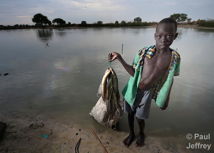 Duot Kuol, 13, displays fish he caught in Poktap, a town in South Sudan's Jonglei State where conflict, drought and inflation have caused severe food insecurity. The Lutheran World Federation, a member of the ACT Alliance, is helping families tackle food problems, including by providing cash for the purchase of fishing line and hooks. This boy's family fled the region when war broke out in 2013, living as refugees in Uganda until returning in 2016.<br /> <br /> Parental consent obtained.