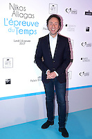 French TV host Stephane Bern poses during a photo call for the opening of a photography exhibition by French-Greek TV host Nikos Aliagas, on January 16, 2017, in Paris.