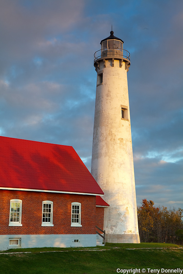 Iosco County, Michigan<br /> Tawas Point Lighthouse (1876) in evening sunlight with clearing storm clouds, Tawas Point State Park, Lake Huron