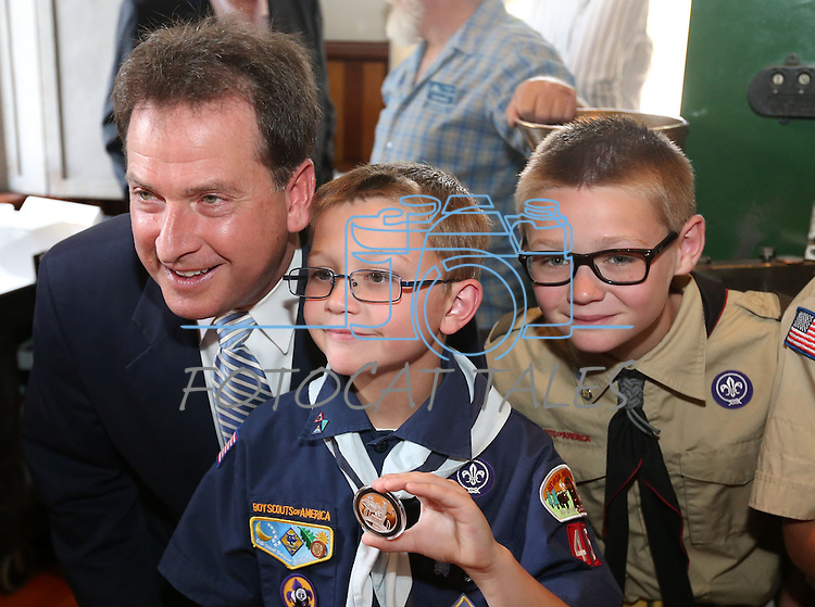 From left, Lt. Gov. Brian Krolicki, Nate Crossman, 9, and Jacob Crossman, 11, pose after a ceremony marking the beginning of production of the third medallion in the four-part Sesquicentennial series, at the Nevada State Museum in Carson City, Nev., on Friday, May 30, 2014. <br /> Photo by Cathleen Allison