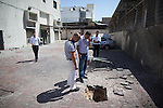 Israelis walk next to damaged shop that was hit by a rocket fired from the Gaza strip in Ashdod, on the second day of Operation Protective Edge, July 9, 2014. Photo by: JINIPIX