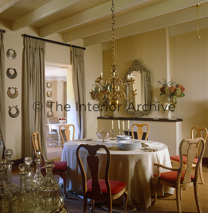 The dining room is decorated with an Indian mirror and antique necklaces and opens onto a small adjacent sitting room