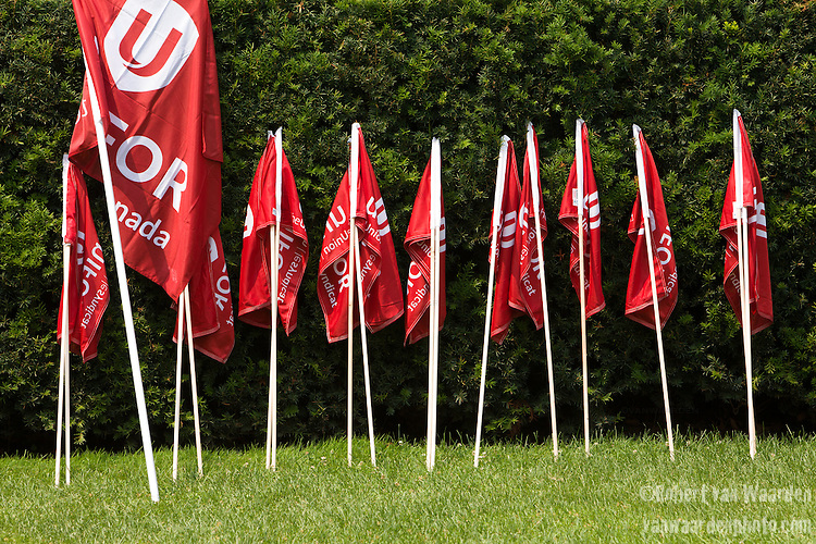 Unifor flags wait for march participants prior to the Jobs, Justice and Climate march in Toronto. On July 5th more than 10,000 people gathered in Toronto, the traditional territories of the Missisauga peoples, for the March for Jobs, Justice and the Climate. The march told the story of a new economy that works for people and the planet. People marched for an economy that starts with justice, creates good work, clean jobs and healthy communities. The people recognize that we have solutions and we know who is responsible for causing the climate crisis. (Photo: Robert van Waarden)