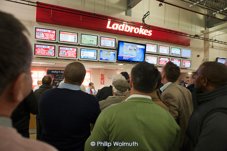 Men watch a televised horse race at a Ladbrokes bookmakers counter at Doncaster racecourse.