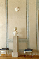 A bust stands on a plinth between a pair of delecate 18th century stools in this marble panelled room