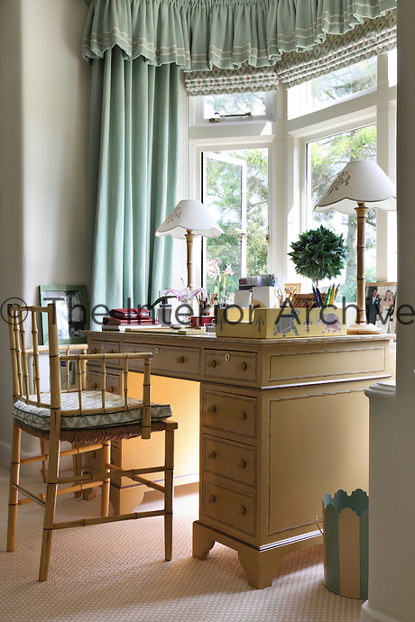 A painted desk and bamboo chair in the bay window of the sitting room