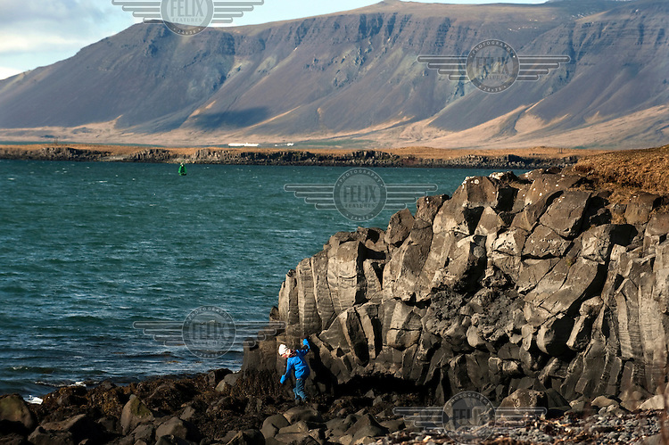 A found girl plays on rocks by the North Atlantic Ocean on the outskirts of Reykjavik.