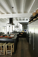 The large kitchen is the hub of the house and the generously proportioned central island is constructed from oak and Belgian stone