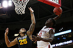 27 November 2015: NC State's Abdul-Malik Abu (0) attempts a dunk over Winthrop's Zach Price (25). The North Carolina State University of North Carolina Wolfpack hosted the Winthrop University Eagles at the PNC Arena in Raleigh, North Carolina in a 2015-16 NCAA Division I Men's Basketball game. NC State won the game 87-79.