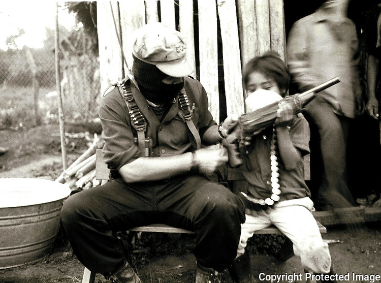 Zapatista rebel leader Subcomandante Marcos delivers his gun to the zapatista boy Beto, late March 22, 1994 somewhere in their stronghold in the Lacandonian jungle. Zapatista rebels uprose on January 1st, 1994 battling against Mexican army. Photo by  Heriberto Rodriguez