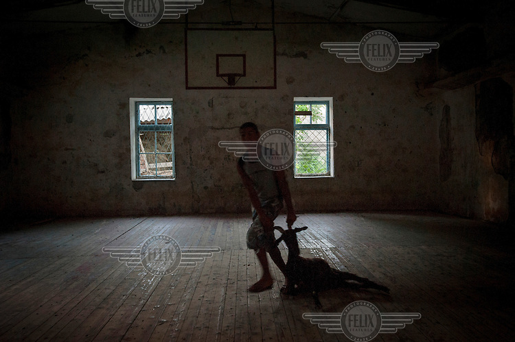 A man drags a goat across the floor of an abandoned gym. Built during the Soviet era it now houses various livestock..