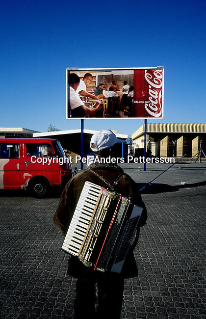 An unidentified musician carries an accordion after playing on the street on August 10, 2001 in Khayelitsha, a township about 35 kilometers outside Cape Town, South Africa. Khayelitsha is one of the poorest and fastest growing townships in South Africa. People usually come from the rural areas in Eastern Cape province to find work as maids and laborers. Most people don't find work and the unemployment rate is high, with lot of violence and a growing HIV-Aids epidemic it's a tough area to live in. (Photo by: Per-Anders Pettersson).