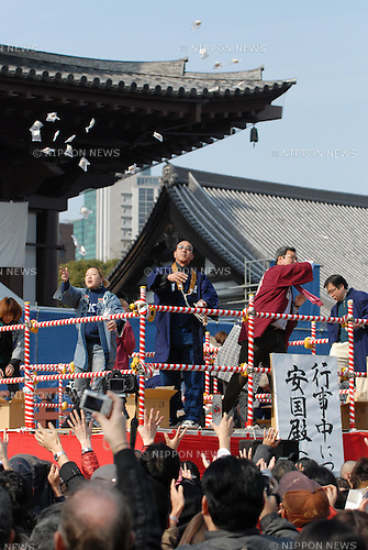 People try to catch thrown roasted soy beans and snacks at Tokyofs Zojoji temple as part of the Setsubun festival which marks the lunar calendar start of spring. The beans are supposed to drive away the evil spirits that bring misfortune and bad health with them.