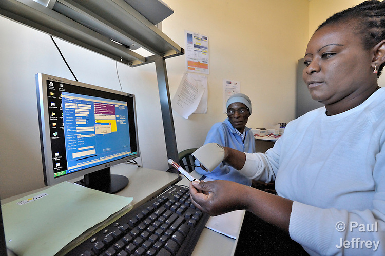 Elizabeth Ntahlaba watches as nurse Frederica Mokyadi Ramashapa inputs information into a computer after drawing her blood at the St. Francis Care Centre ARV Clinic in Johannesburg, South Africa. The test will indicate her T cell count and viral load. The centre is a project of the Roman Catholic Archdiocese of Johannesburg, and is supported by Catholic Relief Services, a member of the Ecumenical Advocacy Alliance.