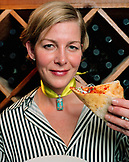 USA, California, Los Angeles, portrait of a mid adult lady holding pizza at Pizzeria Mozza.