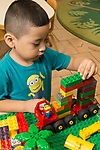 Education Preschool 4 year olds boy building vehicle from plastic connecting blocks