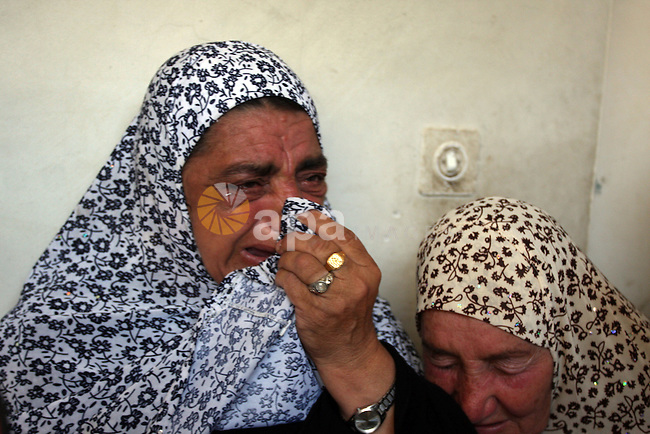 The mother (R) of Naim Najar cries during his funeral  in the West Bank village of Idhna, near Hebron, Sunday, June 17, 2012. An Israeli tow truck driver shot dead two Palestinians and wounded one Sunday during what Israeli police said was an attempted car robbery in the West Bank. The incident occurred near the city of Hebron. Palestinian President Mahmoud Abbas said the shooting was the work of a Jewish settler. Those (settlers) commit their crimes under the protection of the government and Israeli military Abbas said. Photo by Issam Rimawi